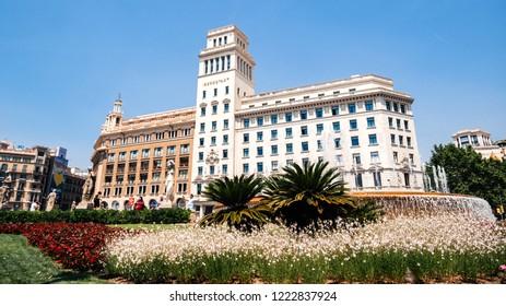 BARCELONA, SPAIN - JUN 1, 2018: Majestic Placa Rambla Catalunya with majestic Iberostar hotel and fountain - wide angle view of the European city warm cinematic color