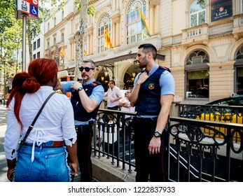 BARCELONA, SPAIN - JUN 1, 2018: Police officers helping locals and tourists people with direction on the iconic Rambla dels Estudis steet