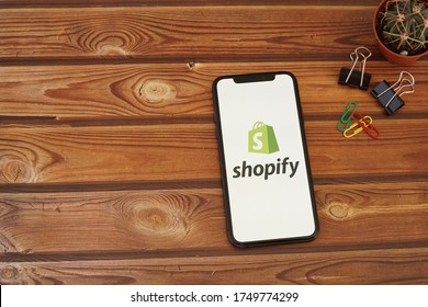 Barcelona, Spain - June 05, 2020; Shopify App with Paper Clips on a Wooden Table. Shopify is a Canadian multinational e-commerce company. #Shopify