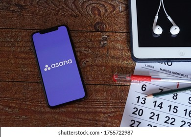 Barcelona, Spain - June 14, 2020; Asana Iphone Screen on a Vintage Table with Calendar and Ipad. Asana is an app to improve team collaboration and work management. #Asana