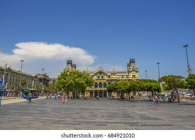 BARCELONA, SPAIN - JUNE 2017: Pedestrian streets across the coastal riviera of Barcelona city, Spain. Centered the central building of the Port of Barcelona. Barcelona, Catalonia, Spain