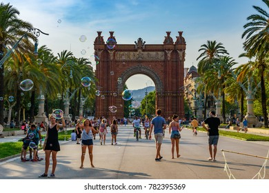 BARCELONA, SPAIN - JUNE 2017: Pedestrians walking accross a soap bubble performer in front of the amazing Arc de Triomf, located in Barcelona, Spain, Europe
