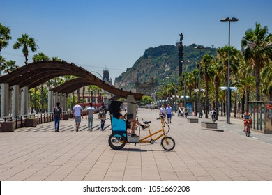 Barcelona, Spain, June 2017: People outdoors, in a rickshaw, on bicycles & walking, taking advantage of warm weather along the city's palm tree lined roads in Barcelona city, Spain, Europe.