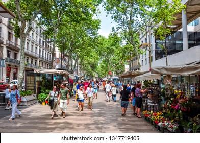 Barcelona, Spain - June 2018: People walking on La Rambla (central street of Barcelona)