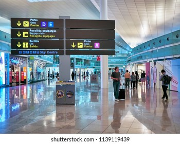 Barcelona, Spain - June 28, 2018.Passengers in transit in a Terminal of Barcelona international airport with a Dutyfree stores in background. Barcelona, Catalonia, Spain.