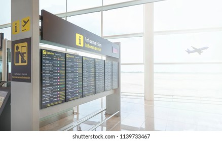 Barcelona, Spain - June 28, 2018. A digital timetable display in a european airport showing flights departures information and a airplane taking off in background.