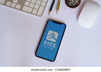 Barcelona, Spain - June 30, 2020; Alipay Iphone Screen with Keyboard and Pencils on a White Desk. Alipay is a third-party mobile and online payment platform. #Alipay