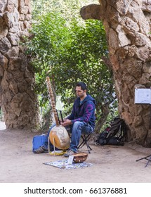 Barcelona, Spain - June 4, 2011: Street artist playing sitar in the Parc Guell. The Park Guell was designed by Antoni Gaudí. In 1984, UNESCO declared the park a World Heritage Site.