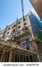 Barcelona, Spain - June 4, 2015: Worker running a construction crane is lifting a container of cement in the construction of a building in the old town of Barcelona