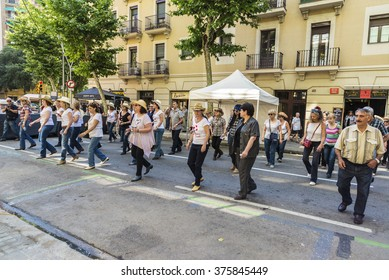 Barcelona, Spain - June 6, 2015: Adult people dancing country in the streets of Barcelona during the holidays