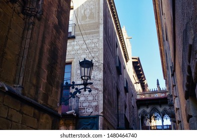 "Barcelona, Spain; June 8, 2017: Croissing point of ""Carrer del Bisbe"" and ""Santa LLùcia"" streets, showing the walls of the Saint Lucy's Chapel of the Cathedral of Barcelona and the Bishop's bridge"