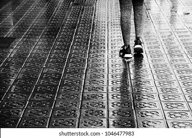 BARCELONA, SPAIN  - MARCH 11, 2018: Adidas popular sneakers shoes on female legs on wet flower street paving. Workout during vacation in Barcelone. Adidas is largest sportswear manufacturer in Europe
