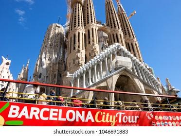 BARCELONA, SPAIN  - MARCH 12, 2018: Barcelona city tour touristic bus near famous Sagrada Familia Basilica yet not finished work of Catalan architect Antoni Gaudi.
