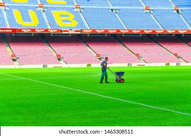 Barcelona, Spain, March 14, 2019: worker is seeding grass with fertilizer spreader on lawn of Camp Nou green field, tribunes stands background. Stadium of football club Barcelona