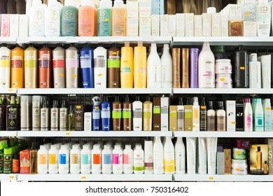 BARCELONA, SPAIN - MARCH 17, 2016: Many hair care products on the large shelves inside retail store with cosmetic products and wigs