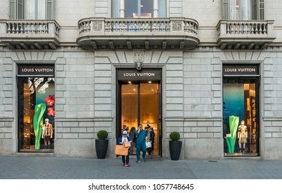 Barcelona, Spain. March 2018: People walking in front of Louis Vuitton shop with in Barcelona's luxury shopping street of Passeig de Gracia. Consumerism concept.