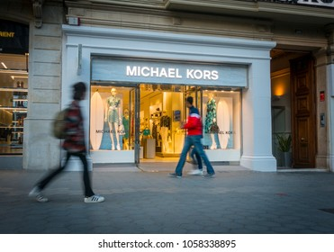Barcelona, Spain. March 2018: People walking in front of Michael Kors shop in Barcelona's luxury shopping street of Passeig de Gracia. Consumerism concept.