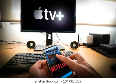 Barcelona, Spain. March 2019: Man holds a smartphone with netflix app and a Pc with the new Apple TVplus on screen on the background. Apple TV is set to compete with other video streaming subscription