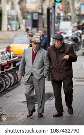 BARCELONA, SPAIN. March 22, 2015: Two elderly men are walking in the city center of Barcelona, Spain. They are talking to each other.