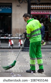 BARCELONA, SPAIN. March 22, 2015: Garbage man is sweeping the road in the city center of Barcelona in Spain. He wears a uniform fluorescent yellow.