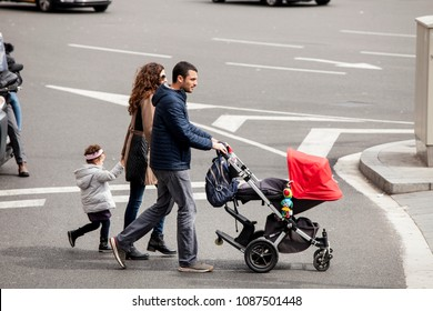 BARCELONA, SPAIN. March 22, 2015: Whole family walking with the stroller through the intersection at the traffic lights on the road in the historic center of Barcelona in Spain.