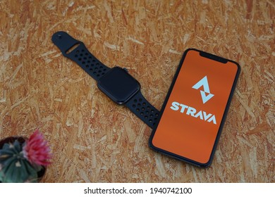 Barcelona, Spain - March 22, 2021: Strava Iphone Apps with iWatch on a Wooden Table.