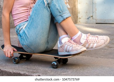 Barcelona, Spain. March 7, 2018: Young woman with skate, wearing old pink  adidas shoes with white stripes on urban background.