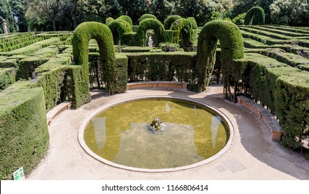 Barcelona, Spain - May 10, 2018: Small circular pond at the exit of the maze of Labyrinth Park of Horta. The central statue of Eros and cypress arches are visible in the background.