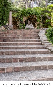 Barcelona, Spain - May 10, 2018: Stone stairs leading to the grotto of the nymph Egeria built by Bagutti in 1804 in Horta Labirinth Park. The sculpture of a sleeping nymph is made of white marble.