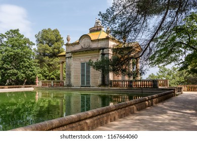 Barcelona, Spain - May 10, 2018: Girl in pink dress is walking near neoclassical pavilion of Carlos IV and a square pond in the Horta Labyrinth Park.