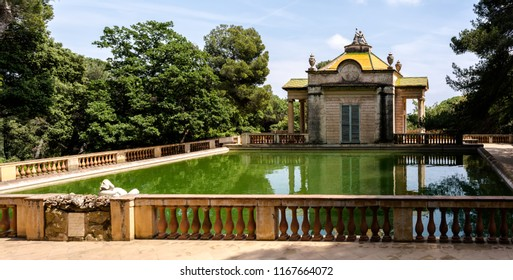 Barcelona, Spain - May 10, 2018: Neoclassical pavilion of Carlos IV and a square pond with fish in the Horta Labyrinth Park. The pavilion was built in 1794 by Domenico Bagutti.