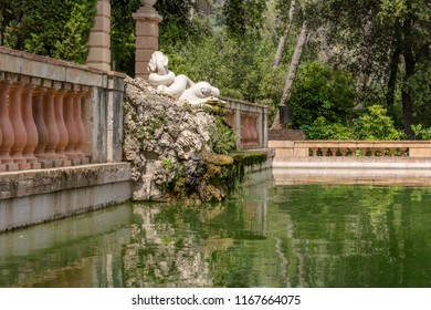 Barcelona, Spain - May 10, 2018: White sculpture of two dolphins with intertwined tails at pond in Horta Labyrinth Park. The sculpture is made of marble on a base of rockery.