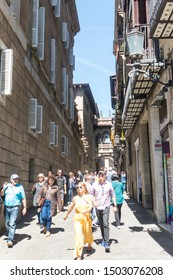BARCELONA, SPAIN - MAY 10, 2019: People walk under the neogothic bridge at Carrer del Bisbe (Bishop Street) in the famous Gothic Quarter. Barcelona, Catalonia, Spain
