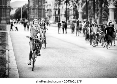 Barcelona, Spain - May 13 2014: Cheerful girl crossing the Promenade Passeig de Lluís Companys on a shared bike.