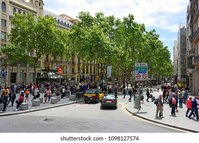 Barcelona, Spain - May 13, 2018:  Entrance to La Rambla with signs for pacification of traffic and preference of bikes.  It is a popular tree-lined pedestrian mall stretching 1.2 km.