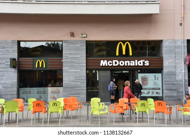 Barcelona, Spain - May 13, 2018:  McDonalds restaurant with chairs and tables on the sidewalk of street across from the Sagrada Familia.