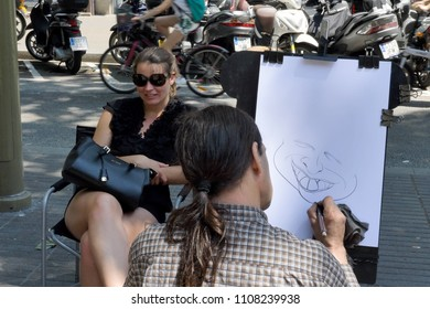 Barcelona, Spain - May 15, 2018: Caricature artist draws a portrait of a young lady on La Rambla street, in the heart of Barcelona.