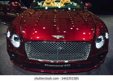 Barcelona, Spain - May 17, 2019: New red luxurious cabriolet Bentley Continental GTC with shining lights reflected at the bonnet