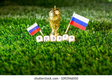 Barcelona, Spain, May 2018: Fifa World Cup concept illustrative editorial. Golden trophy, russian flags and over green grass.