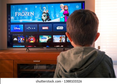 Barcelona, Spain. May 2019: Back view image of cute little boy watching the new Disney plus streaming service on TV.Illustrative editorial