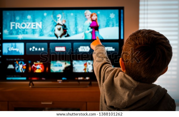 Barcelona, Spain. May 2019: Back view image of cute little boy watching the new Disney plus streaming service and pointing at the TV screen.Illustrative editorial