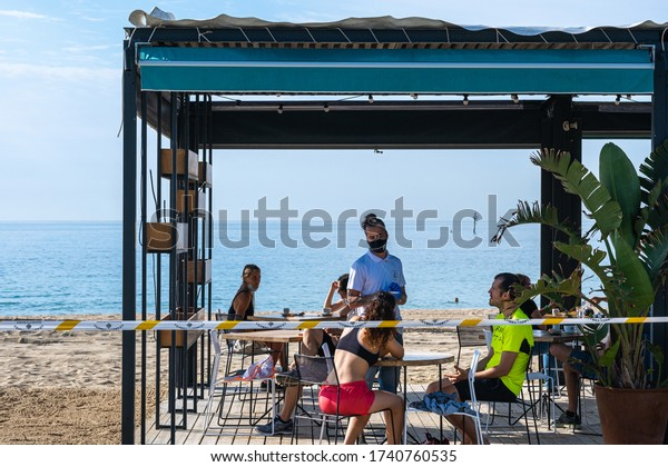 BARCELONA, SPAIN - MAY 25th 2020: First day of the phase 1 of the coronavirus disease (COVID-19) in Barcelona, first day the terraces open at 50% of their capacity and a waiter with a mask