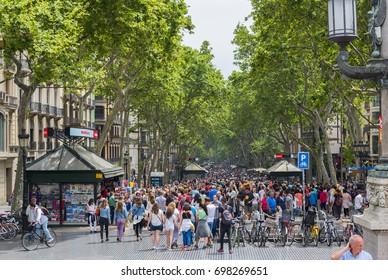 BARCELONA, SPAIN - MAY 27, 2016: La Rambla Street in central Barcelona, Spain. Street is popular for tourists and locals alike.