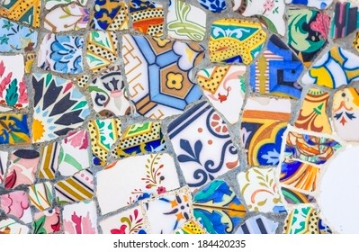 """BARCELONA, SPAIN - MAY 31, 2013: Famous colorful ceramic mosaics detail, designed by Antonio Gaudi and better known as """"trencadis"""". Located in the Park Guell"""