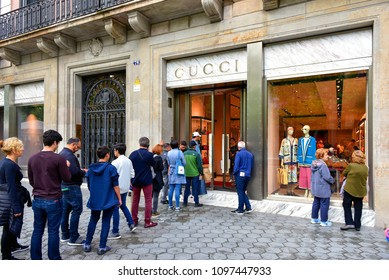 Barcelona, Spain - May 5, 2018:  People wait in line to enter the Gucci, the Italian luxury brand store on Passeig de Gràcia.