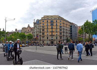 Barcelona, Spain - May 5, 2018:  People ride electric Segway scooters through intersection of Passeig de Gràcia a high end shopping area.  Casa Battlo is to the left of the building on the corner.
