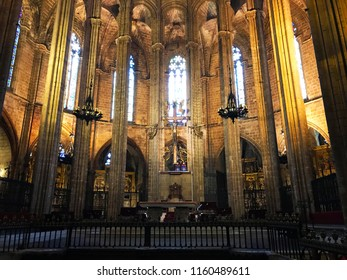 Barcelona, Catalonia, Spain - May/2018 - Main altar of the cathedral of Barcelona. Sculpture of crucified Christ, colorful stained glass and neogothic columns. UNESCO World Heritage.