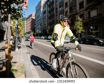 Barcelona, Spain - Nov 12, 2017: Senior couple cycling in central Barcelona early in the morning wearing helmets
