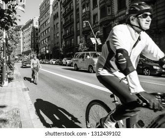 Barcelona, Spain - Nov 12, 2017: Senior couple cycling in central Barcelona early in the morning wearing helmets black and white