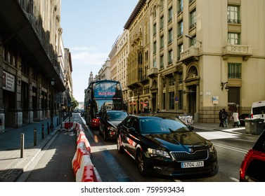 BARCELONA, SPAIN - NOV 12, 2017: Ruta Roja Sightseeing Barcelona Hop On Hop Off bus with tourists and Skoda Superb car in traffic jam in Barcelona